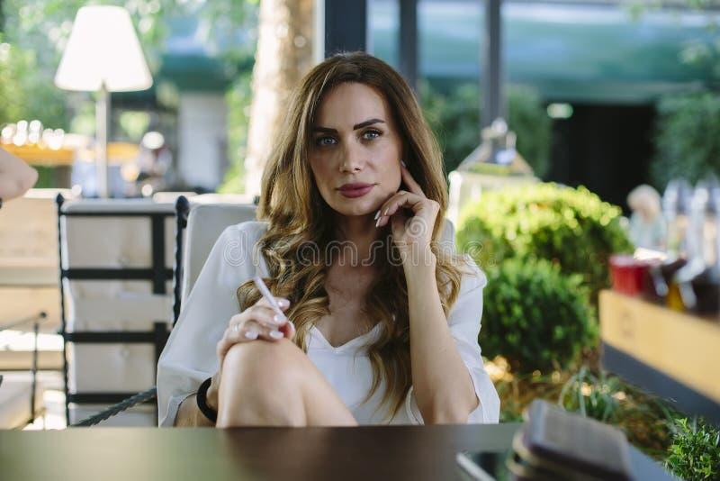 La giovane donna fuma un sigaro ad un ristorante fotografia stock