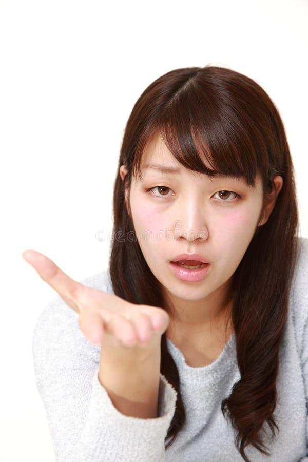 La giovane donna giapponese arrabbiata richiede qualcosa fotografie stock