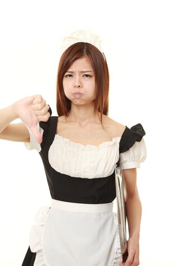 La giovane donna giapponese che porta il costume francese della domestica con i pollici giù gesture fotografia stock libera da diritti
