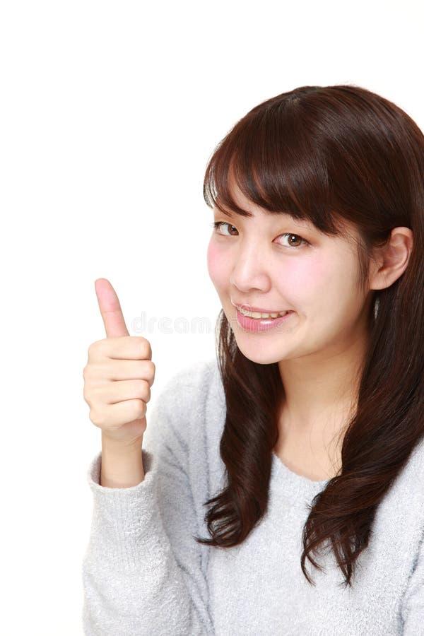 La giovane donna giapponese con i pollici aumenta il gesto fotografie stock