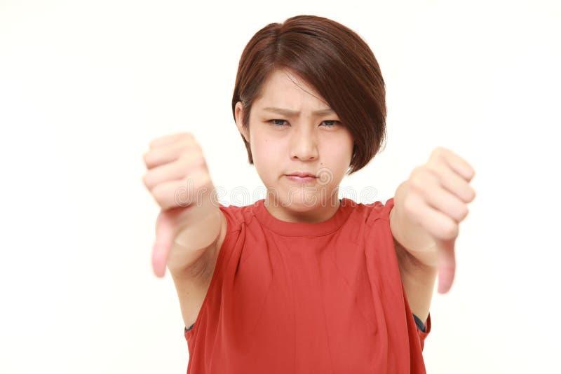 La giovane donna giapponese con i pollici giù gesture fotografia stock libera da diritti