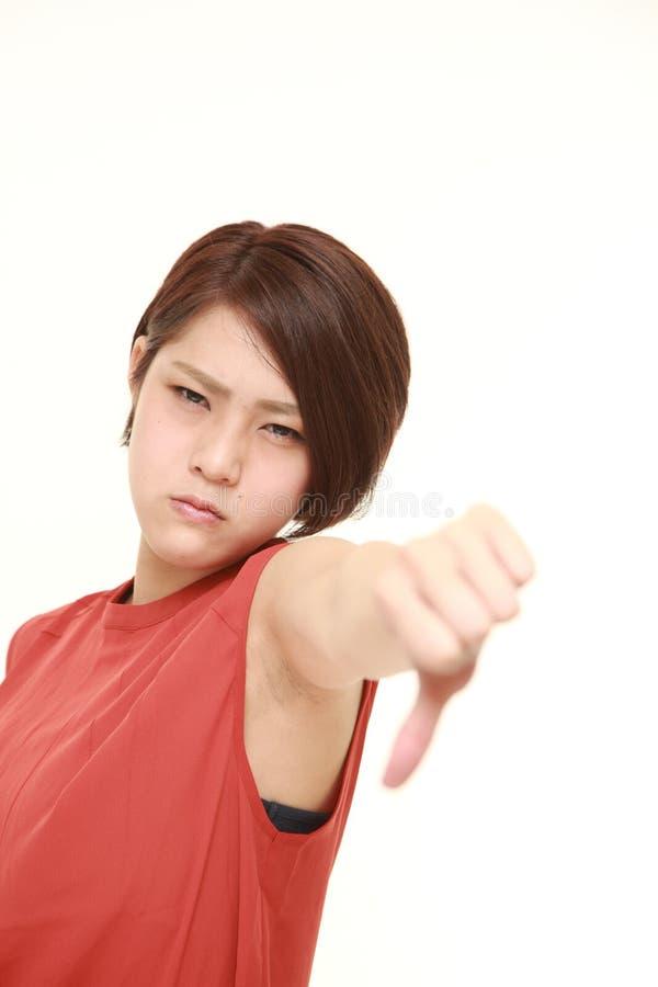 La giovane donna giapponese con i pollici giù gesture fotografie stock libere da diritti
