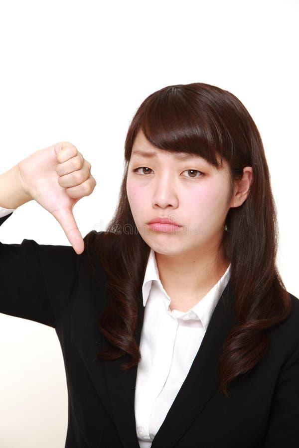 La giovane donna giapponese con i pollici giù gesture immagini stock