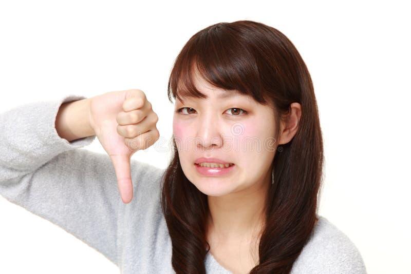 La giovane donna giapponese con i pollici giù gesture fotografia stock