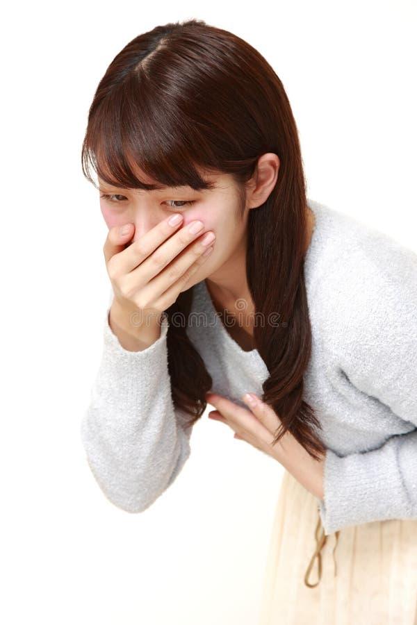 La giovane donna giapponese ritiene come vomitare fotografia stock