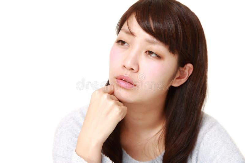 La giovane donna giapponese si preoccupa per qualcosa immagine stock