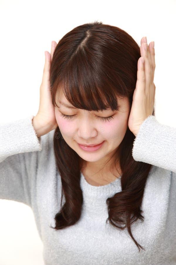 La giovane donna giapponese soffre da rumore immagini stock