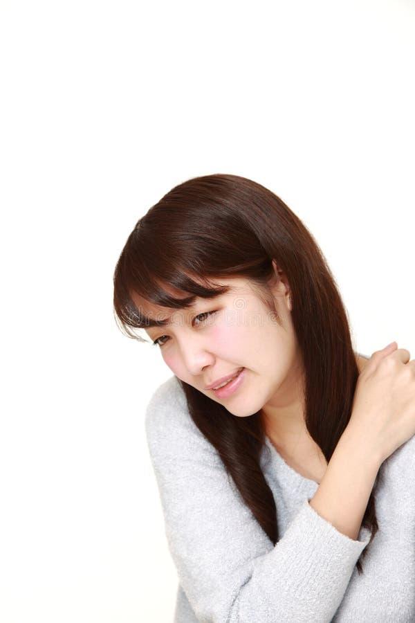 La giovane donna giapponese soffre dal dolore del collo fotografie stock