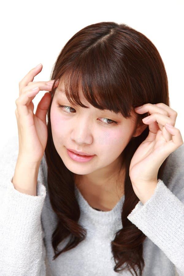 La giovane donna giapponese soffre dall'emicrania fotografia stock