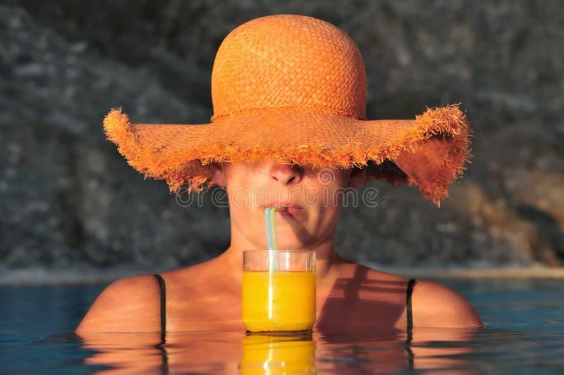 La giovane donna gode della bevanda fredda in raggruppamento fotografia stock libera da diritti