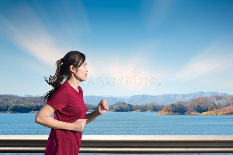La giovane donna gode di di correre fuori con l'estate bella nel lago fotografia stock