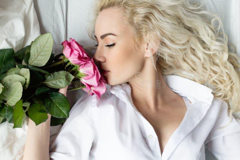 La giovane donna gode di un mazzo dei fiori a letto fotografia stock