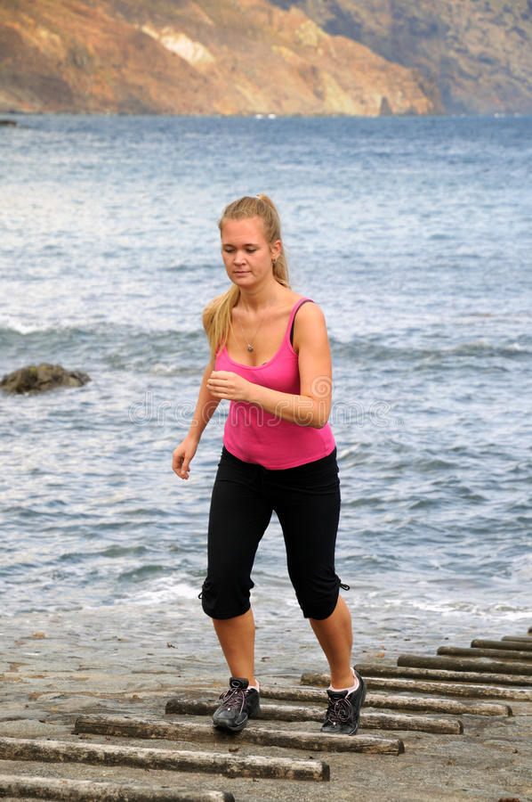 La giovane donna graziosa che fa lo sport si esercita dal mare immagine stock