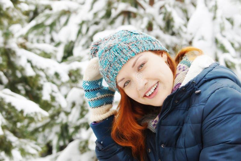 La giovane donna graziosa della testarossa si rallegra di aria fresca nella foresta dell'inverno immagini stock