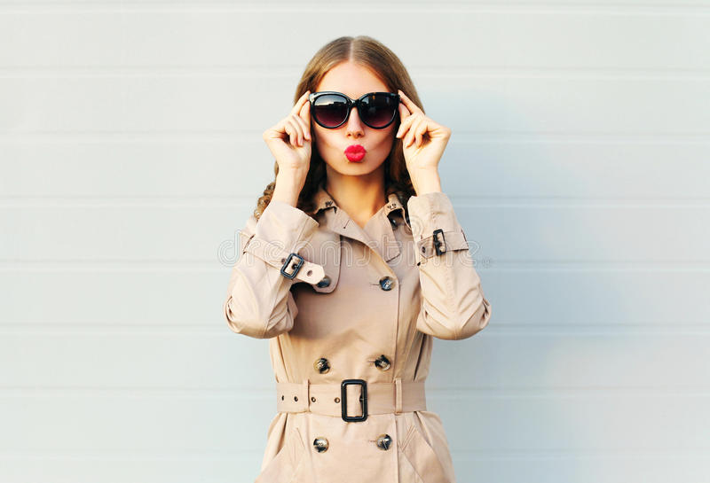La giovane donna graziosa elegante di modo che soffia l'uso rosso delle labbra occhiali da sole neri ricopre sopra grey fotografia stock