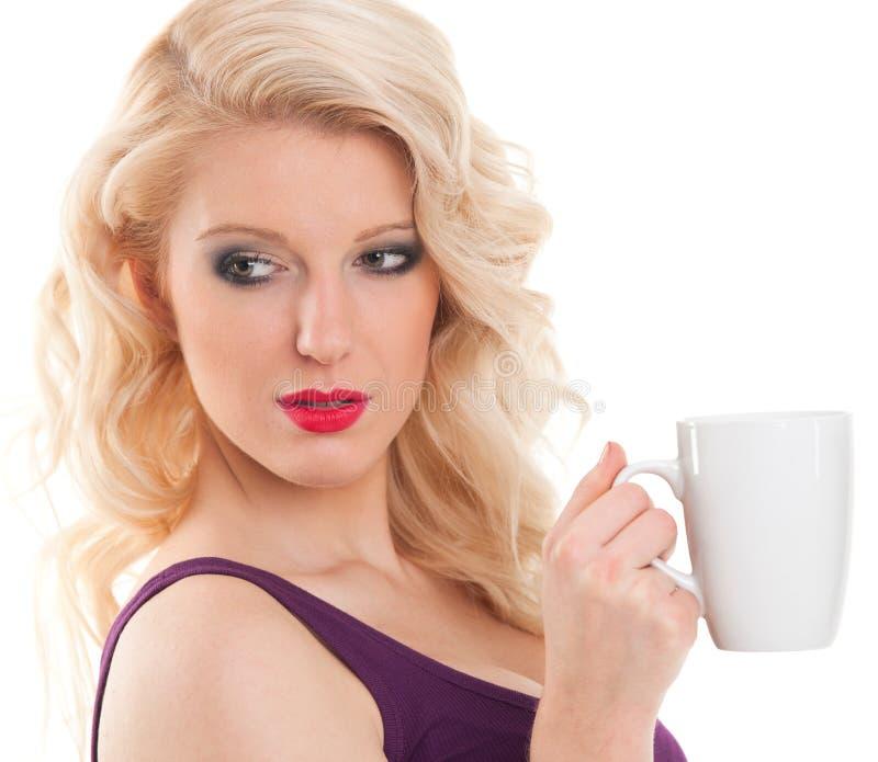 La giovane donna graziosa in maglietta porpora sta tenendo la tazza di caffè immagine stock libera da diritti