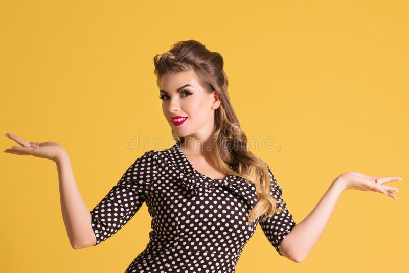 La giovane donna graziosa in retro vestito nero con la pettinatura sta fotografia stock libera da diritti