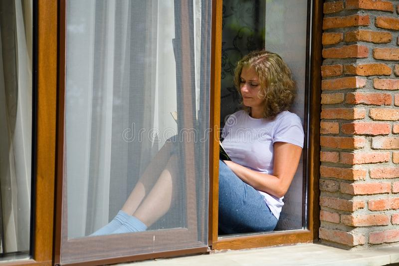 La giovane donna graziosa si siede sul davanzale e legge un libro fotografia stock libera da diritti