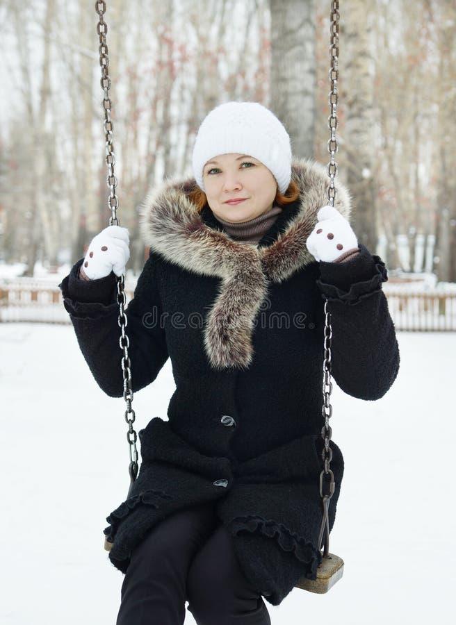 La giovane donna graziosa si siede sull'oscillazione in un parco dell'inverno fotografia stock libera da diritti