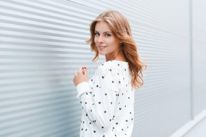 La giovane donna graziosa in un bello sorriso con un'acconciatura alla moda in un maglione d'annata sta vicino alle costruzioni m immagini stock libere da diritti