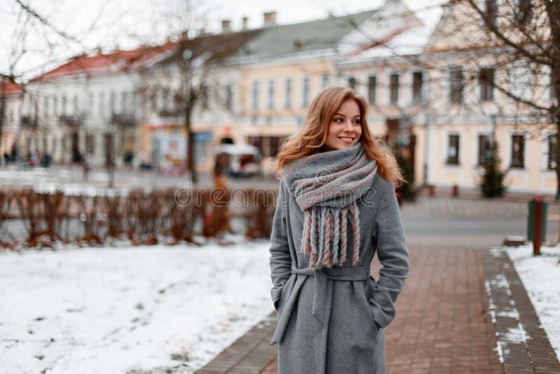La giovane donna graziosa urbana con un bello sorriso in un cappotto alla moda grigio in una sciarpa calda tricottata cammina int immagini stock libere da diritti