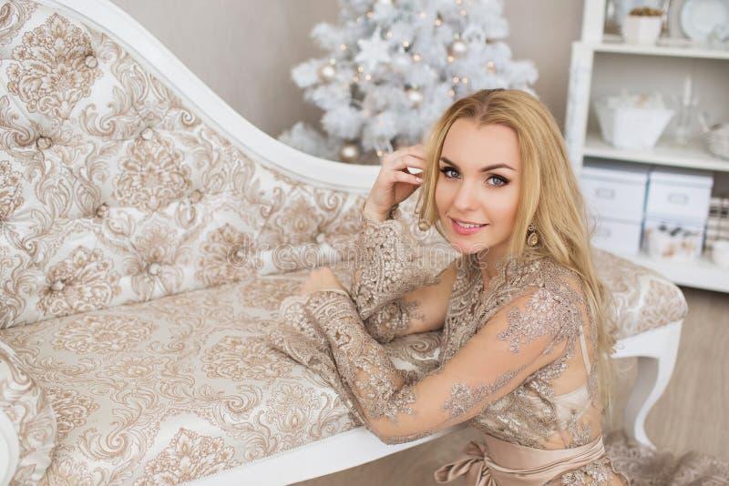 La giovane donna graziosa in vestito da sera si siede su un pavimento nel Natale immagine stock