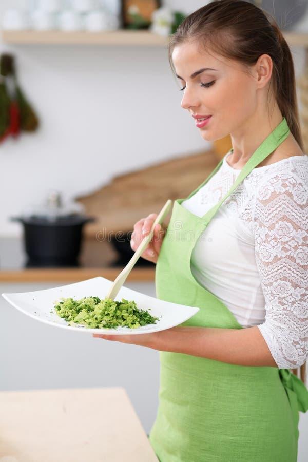 La giovane donna in grembiule verde sta cucinando in una cucina La casalinga sta assaggiando l'insalata fresca dal cucchiaio di l fotografia stock libera da diritti