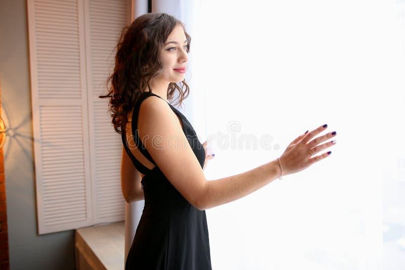 La giovane donna guarda fuori la finestra immagini stock libere da diritti