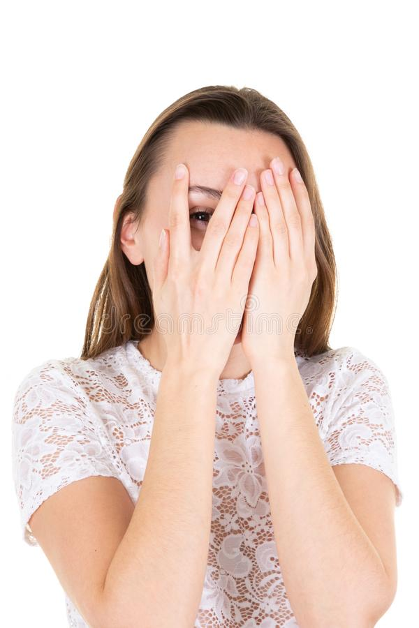 La giovane donna ha coperto il fronte di chiusura di mani e lo sguardo da un occhio tramite le sue dita nel fondo bianco immagini stock