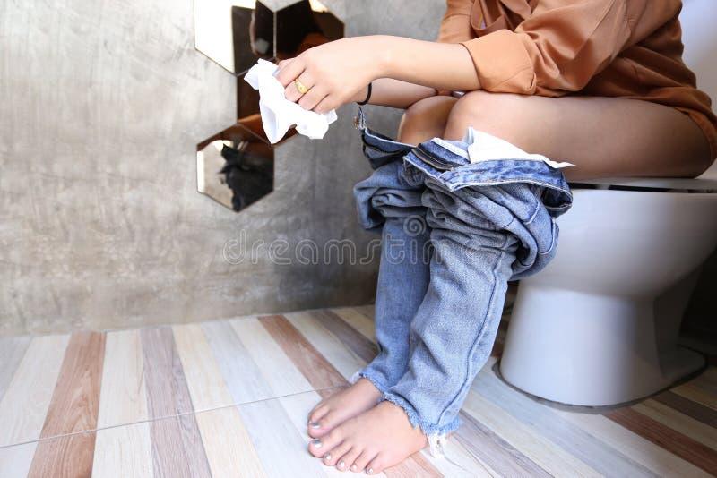 La giovane donna ha la costipazione o emorroidi che si siede sulla toilette, H immagini stock