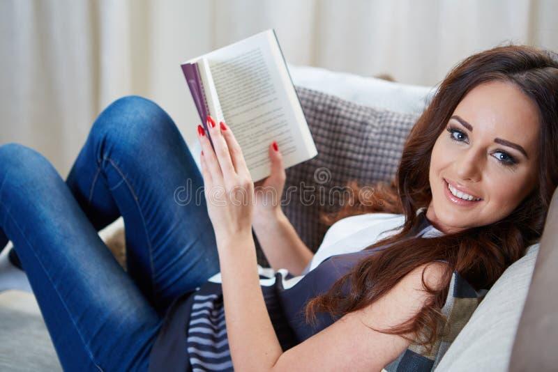 La giovane donna ha letto il libro che si distende sul sofà immagine stock