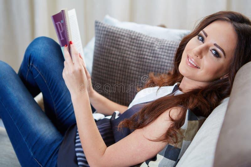 La giovane donna ha letto il libro che si distende sul sofà fotografia stock