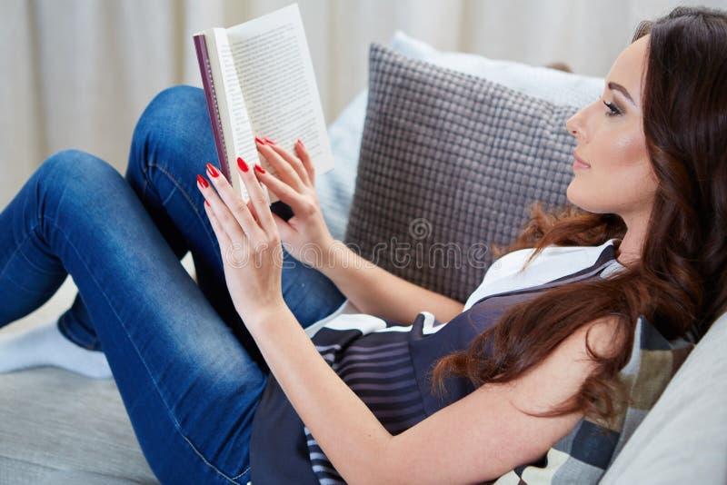La giovane donna ha letto il libro che si distende sul sofà immagini stock