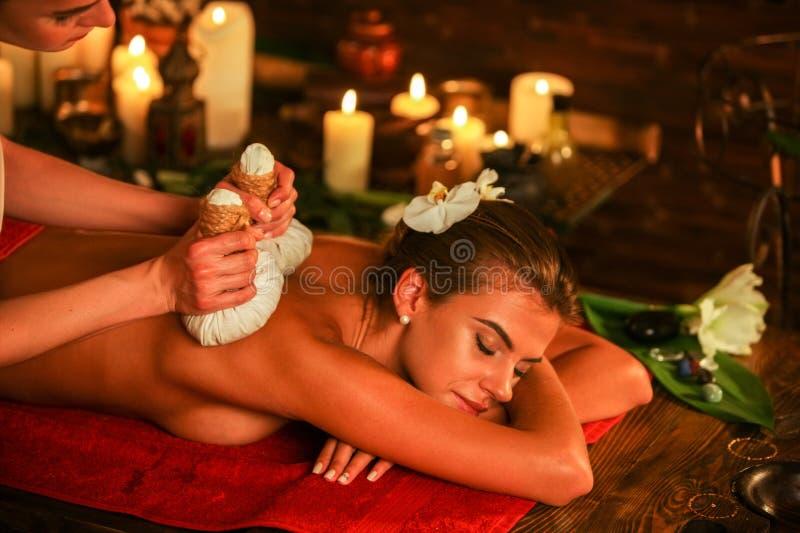 La giovane donna ha massaggio caldo del cataplasma nel salone della stazione termale fotografie stock libere da diritti