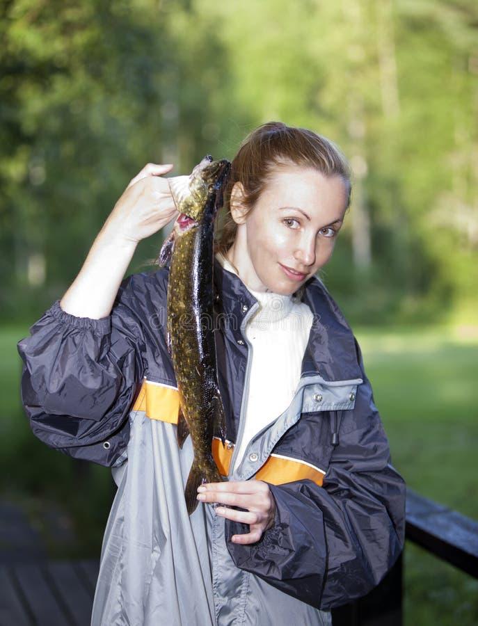 La giovane donna il pescatore con il luccio preso fotografia stock libera da diritti