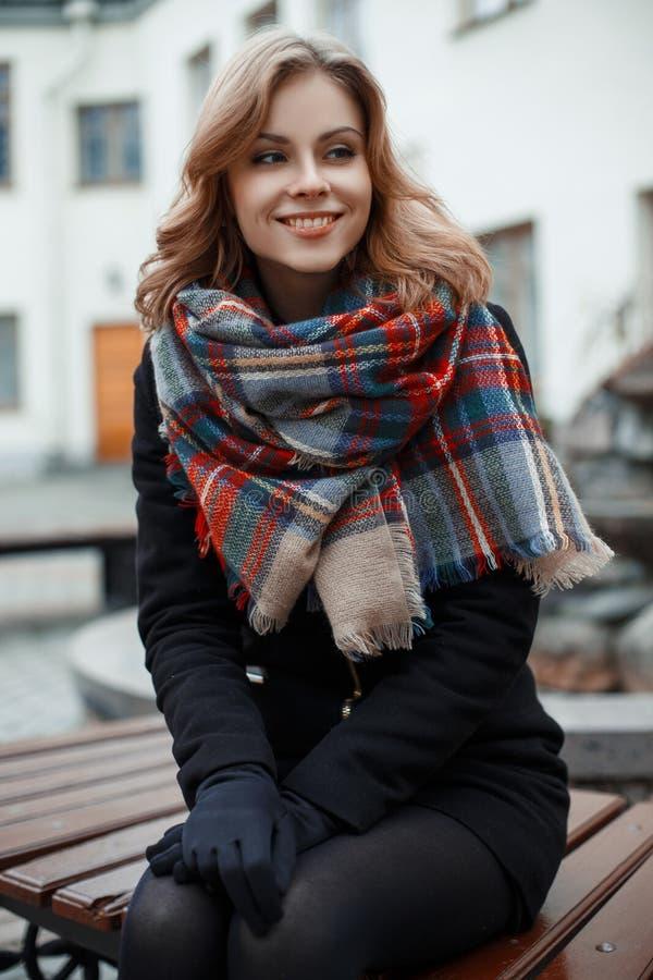 La giovane donna incantante con un bello sorriso in vestiti caldi alla moda sta sedendosi su un banco di legno e su un sorridere fotografia stock libera da diritti