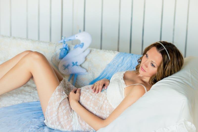 La giovane donna incinta attraente con una bella pancia si trova sullo strato con una cicogna del giocattolo immagini stock libere da diritti