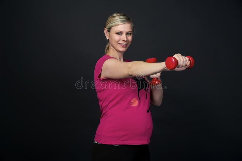 La giovane donna incinta blondy nel rosa t-breve con il gatto fa gli esercizi con le teste di legno rosse di forma fisica, fondo  fotografia stock