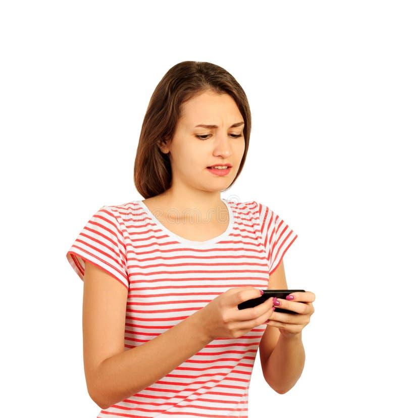 La giovane donna infelice scrive un messaggio sul telefono ragazza emozionale isolata su fondo bianco immagini stock libere da diritti