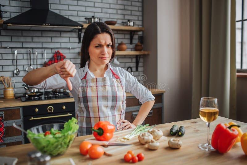 La giovane donna infelice si siede alla tavola in cucina Considera la macchina fotografica e tiene il grande pollice La donna dep immagini stock libere da diritti