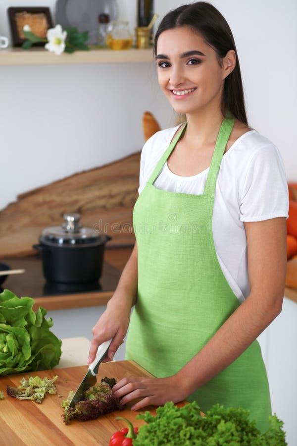 La giovane donna ispanica sta cucinando nella cucina La casalinga sta tagliando le verdure e la carne verde per insalata fresca fotografia stock