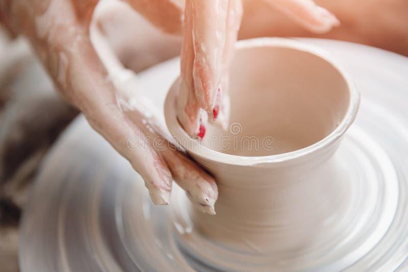 La giovane donna lavora dietro il tornio da vasaio con la lunghezza, facente il piatto fatto a mano Concetto di concentrazione, m immagine stock
