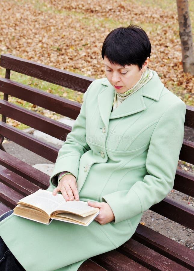 La giovane donna legge il libro nella sosta di autunno immagini stock