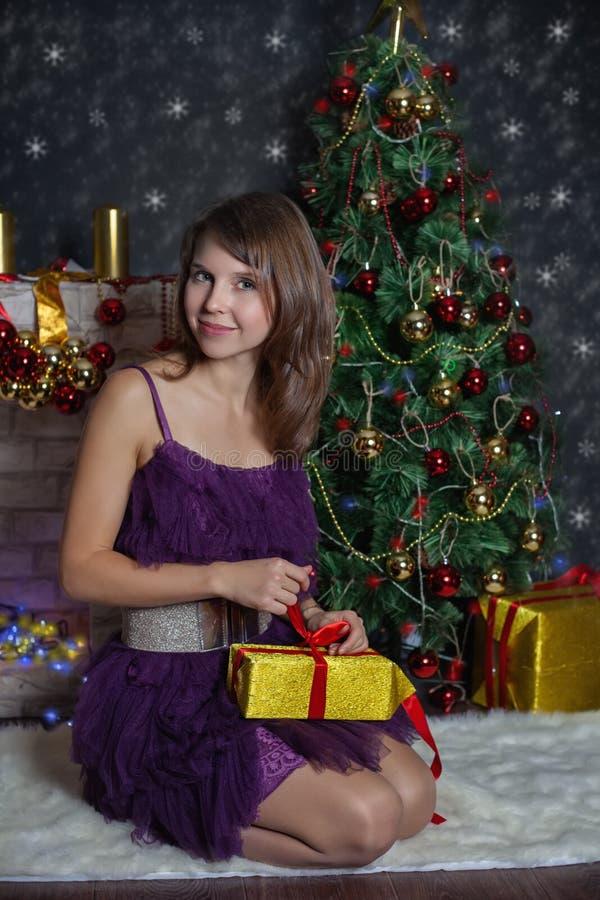 La giovane donna libera il regalo Scene di Natale immagini stock