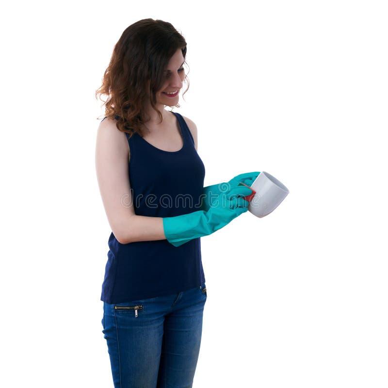 La giovane donna in maglietta scura ed i guanti di gomma verdi sopra bianco hanno isolato il fondo fotografia stock