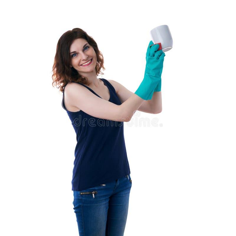 La giovane donna in maglietta scura ed i guanti di gomma verdi sopra bianco hanno isolato il fondo immagine stock