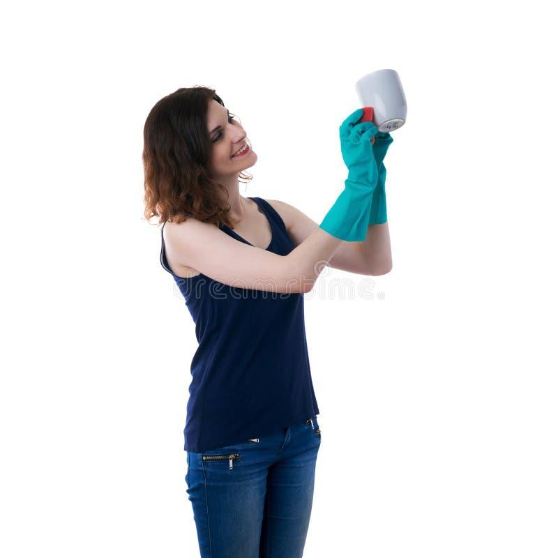 La giovane donna in maglietta scura ed i guanti di gomma verdi sopra bianco hanno isolato il fondo fotografia stock libera da diritti