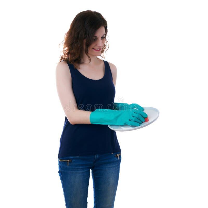 La giovane donna in maglietta scura ed i guanti di gomma verdi sopra bianco hanno isolato il fondo immagini stock