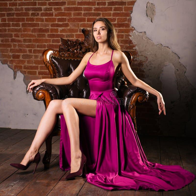 La giovane donna magnifica in vestito lussuoso sta sedendosi in una sedia in un appartamento di lusso Interno d'annata classico fotografia stock libera da diritti