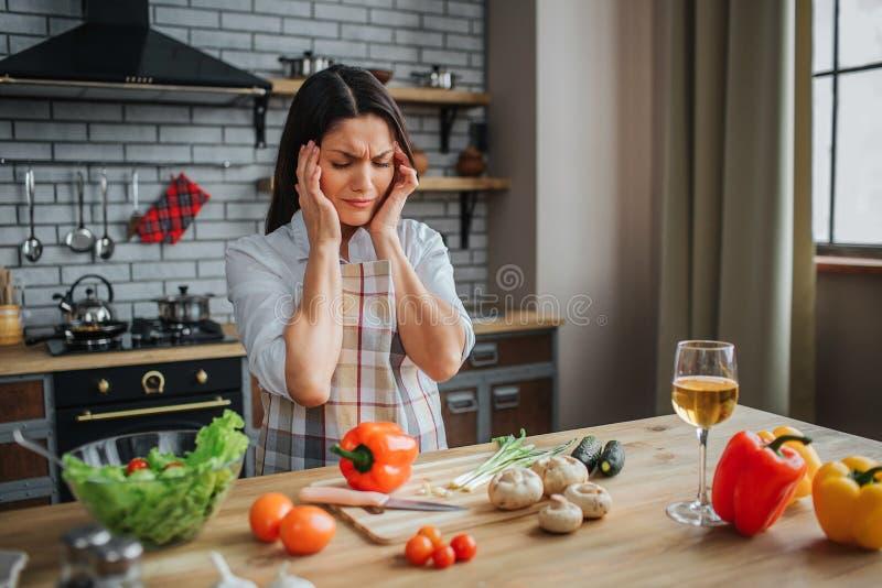 La giovane donna malata ha emicrania Si tiene per mano sulla testa Si siede in cucina alla tavola Tatto della donna cattivo Verdu fotografie stock